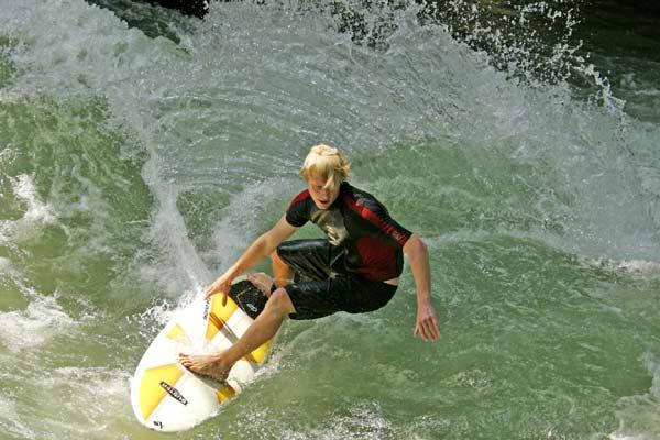 Surfer Gerry Schlegel auf der Eisbach-Welle im Englischen Garten in München. Foto: Flohagena.com